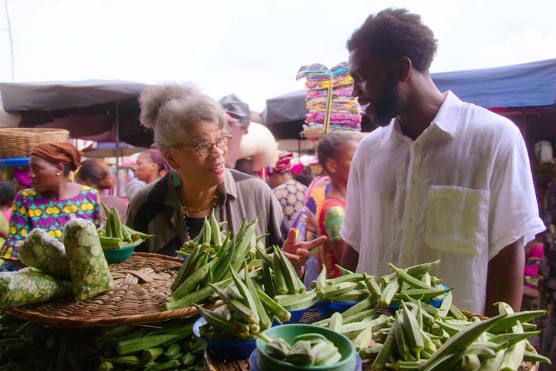 Two people stand in a market talking to each other over bins of okra.