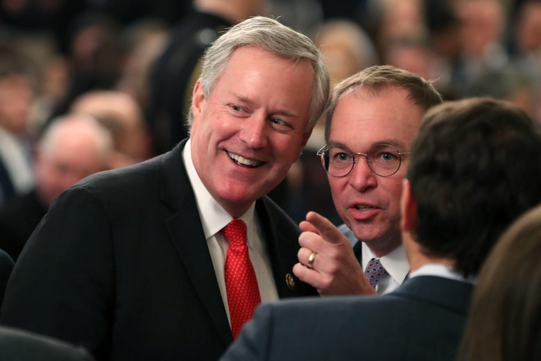 Mick Mulvaney and Rep. Mark Meadows talk as they wait for President Donald Trump to speak to the media.