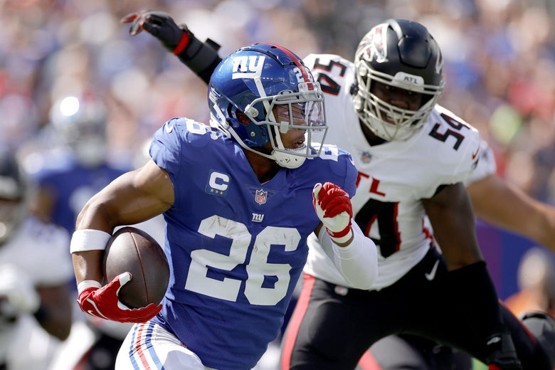 Saquon Barkley #26 of the New York Giants runs for a first down while being chased by Foyesade Oluokun #54 of the Atlanta Falcons at MetLife Stadium.