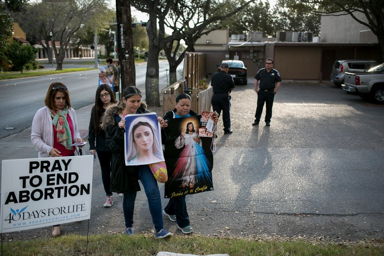 Anti-abortion protesters hold signs bearing religious images and messages while security guards stand by in front of the clinic.