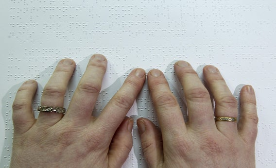 A blind person reads a book written in braille.