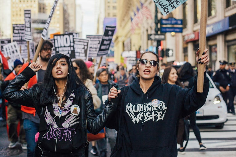 Demonstrators hold signs while marching.