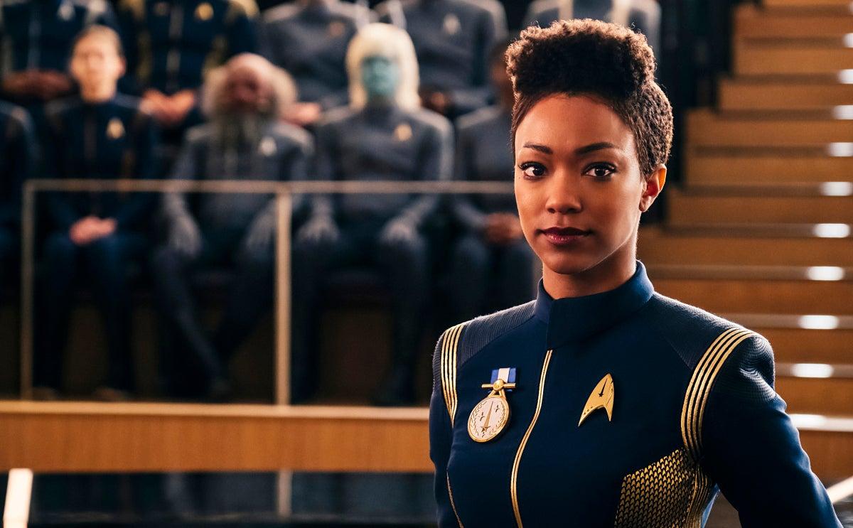 Sonequa Martin-Green as Michael Burnham wears a blue Starfleet uniform with a medal pinned on her chest