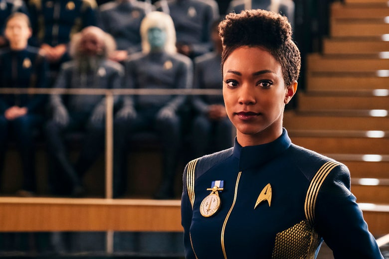 Sonequa Martin-Green as Michael Burnham wears a blue Starfleet uniform with a medal pinned on her chest