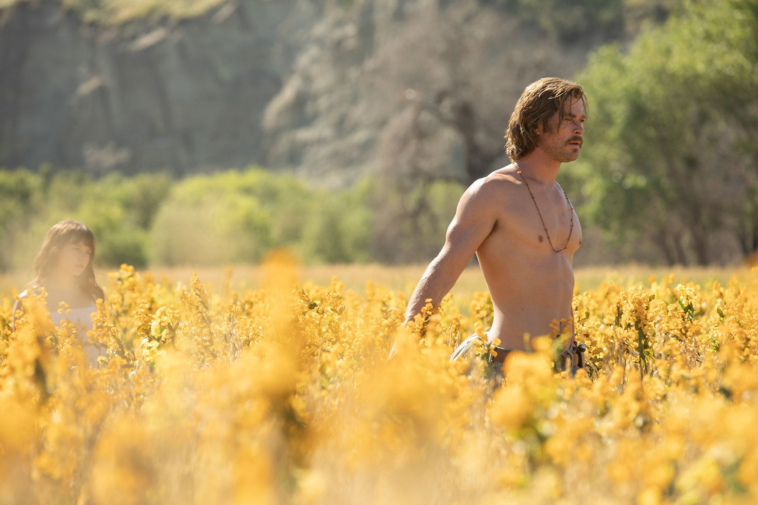 Cailee Spaeny and Chris Hemsworth (shirtless) walk through a field of wildflowers.