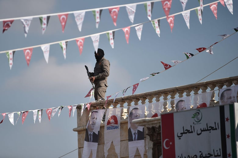 TOPSHOT - A Turkish-backed Syrian rebel fighter stands guard on a roof decorated with posters picturing Turkish President Recep Tayyip Erdogan during a demonstration in support to Turkish army's Olive Branch operation in the Syrian town of Suran on February 1, 2018.         Clashes raged between Turkish-backed forces and Kurdish militia in Syria's Afrin region on January 31, 2018, as wounded civilians fled intense Turkish air strikes. Turkey and allied Syrian rebels have pressed on with Operation Olive Branch in the Kurdish-controlled Afrin enclave despite mounting international concern and reports of rising civilian casualties.          / AFP PHOTO / OZAN KOSE        (Photo credit should read OZAN KOSE/AFP/Getty Images)