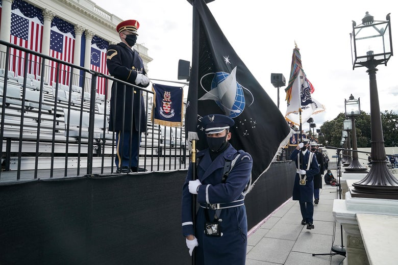 A member of the Air Force holding a Space Force flag walks along the inaugural platform at the Capitol on a cloudy day