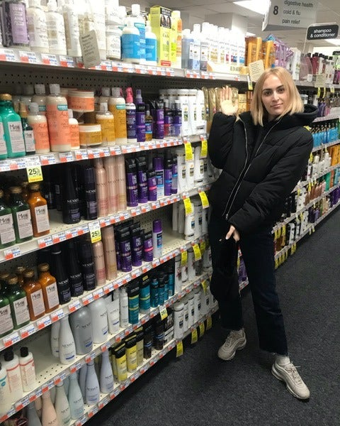 Woman gesturing toward beauty products in a drugstore aisle.