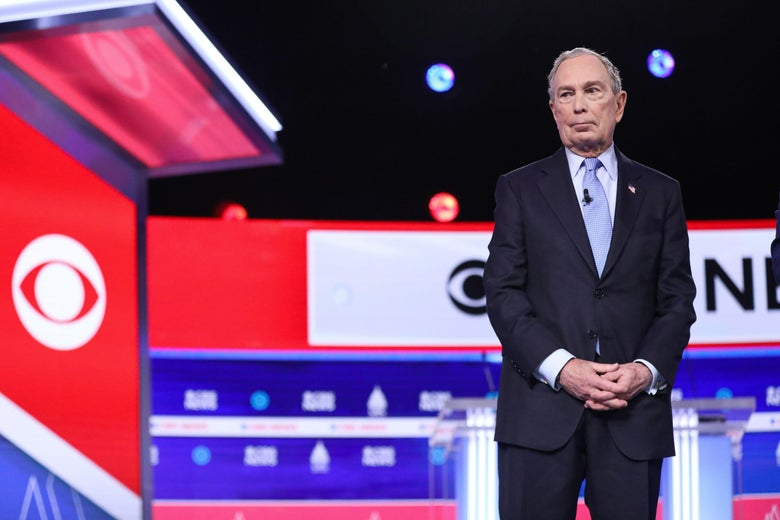Bloomberg stands with his hands clasped on the debate stage.