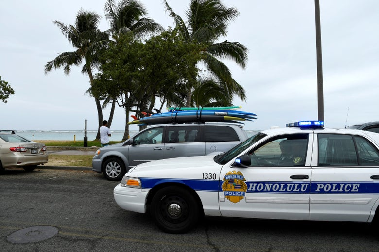 A Honolulu police car is parked in front of another car carrying surfboards. Palm trees and the beach are seen beyond that.