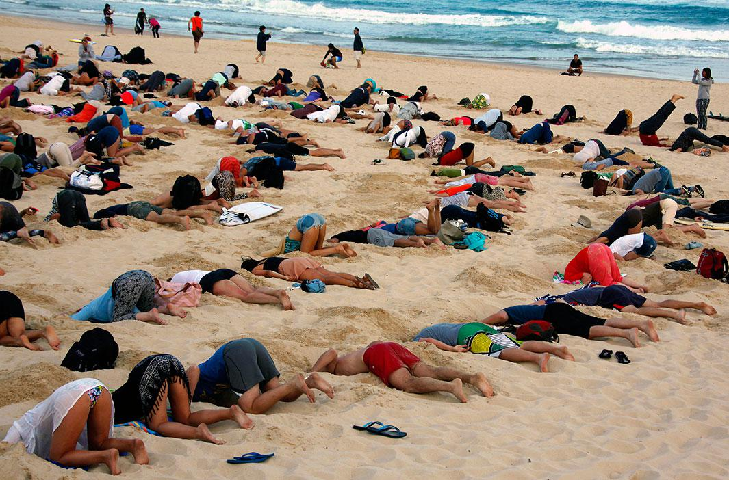 "About 400 demonstrators participate in a protest by burying their heads in the sand at Sydney's Bondi Beach on Nov. 13, 2014. The protest, held ahead of Saturday's G20 summit in Brisbane, was being promoted as a message to Australian Prime Minister Tony Abbott's government that, ""You have your head in the sand on climate change."""
