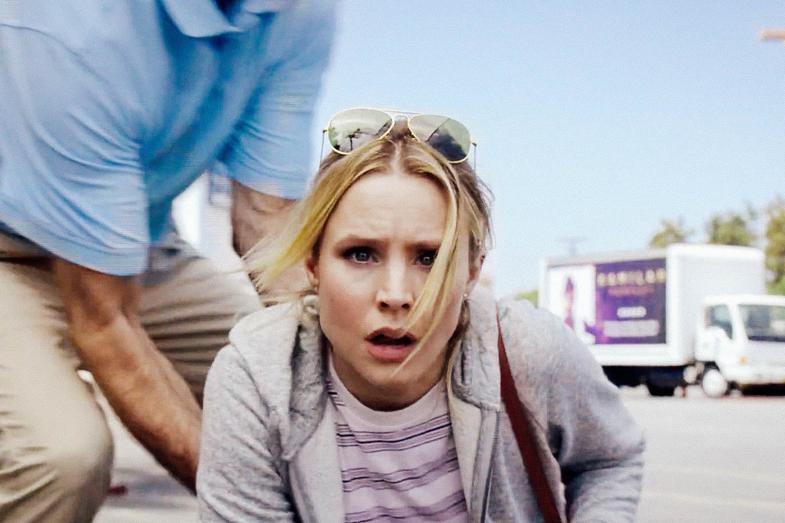 In a scene from The Good Place, Eleanor Shellstrop, played by Kristen Bell, looks dazed as she gets to her feet in a parking lot. A man in a blue polo helps her up, and a truck can be seen in the background.