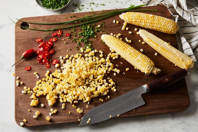 Corn on a cob with some of it shucked, chopped red pepper, and chopped scallions on a wooden cutting board.