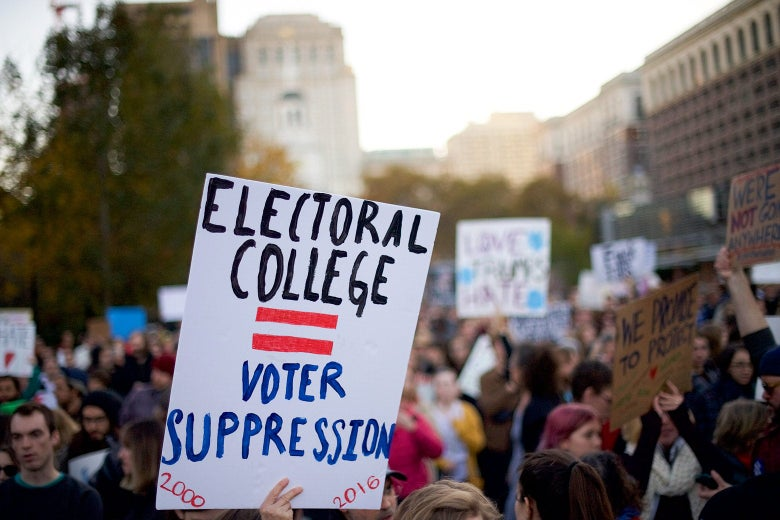 "A protester in a crowd holds up a sign that says ""Electoral College = Voter Suppression."""