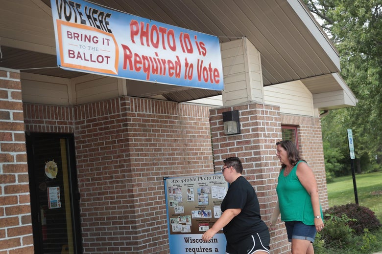 Two people walk into a polling place that has a sign out front warning voters that photo ID is required to vote.