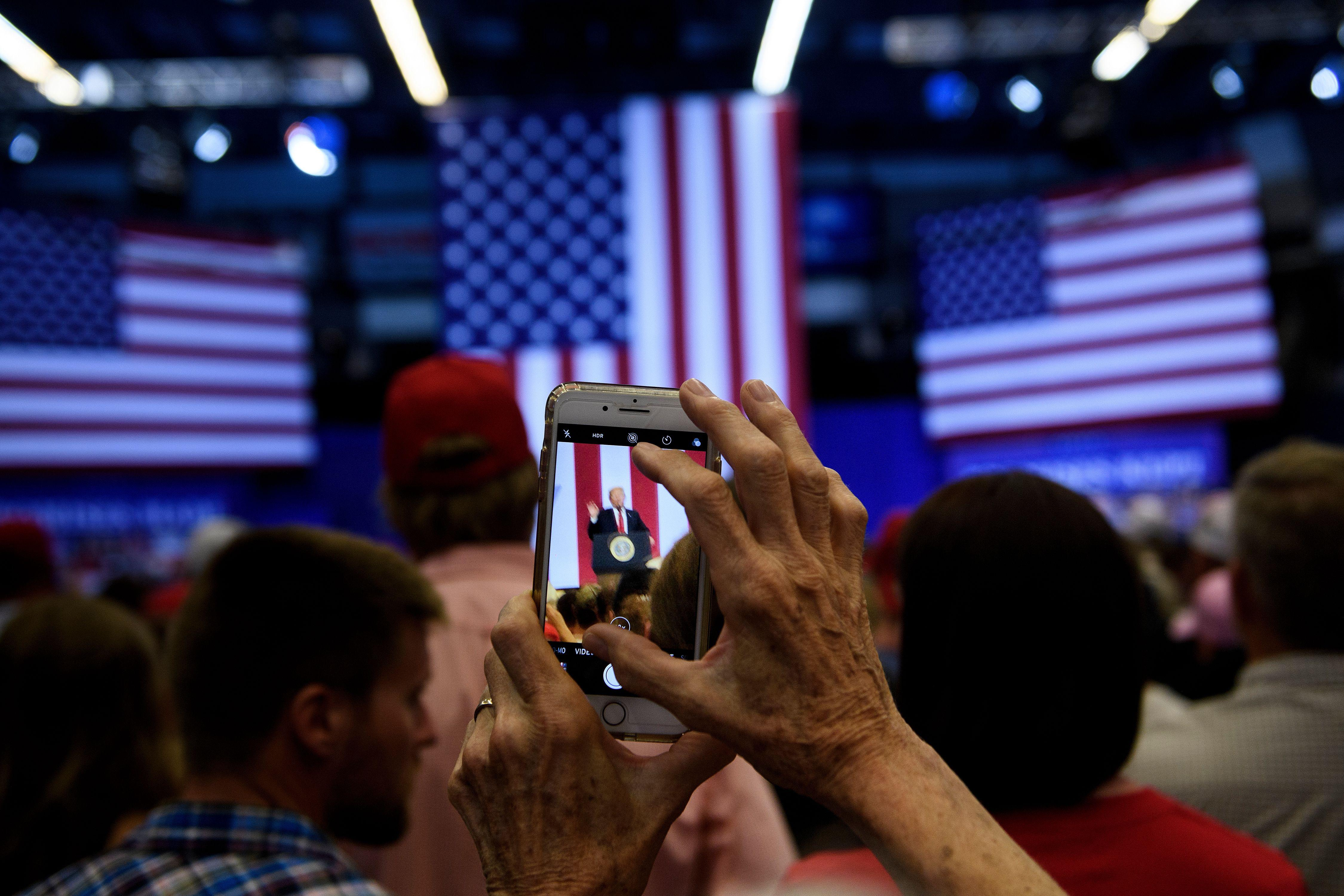 A woman takes a photo as US President Donald Trump speaks during a rally for Rep. Kevin Cramer (R-ND) on June 27, 2018 in Fargo, North Dakota.
