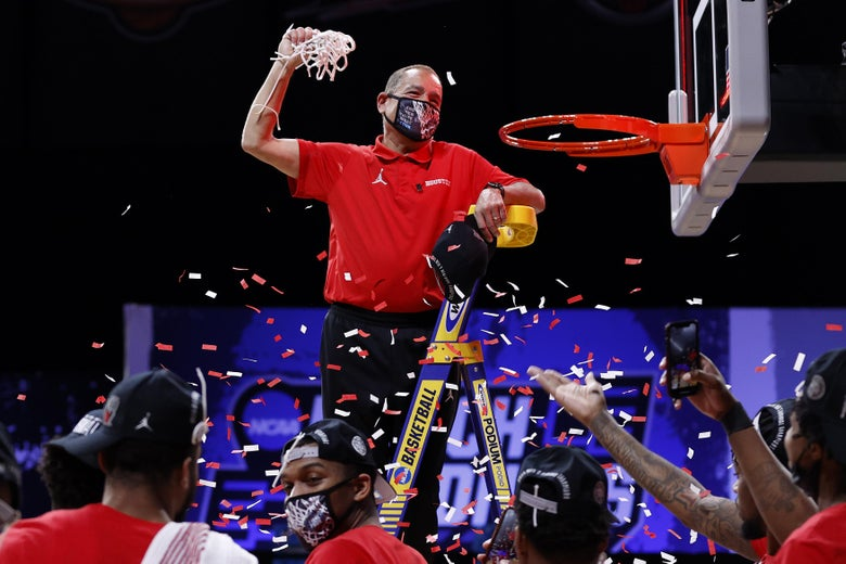 Houston coach Kelvin Sampson stands on a ladder and holds a net as confetti flies around him.