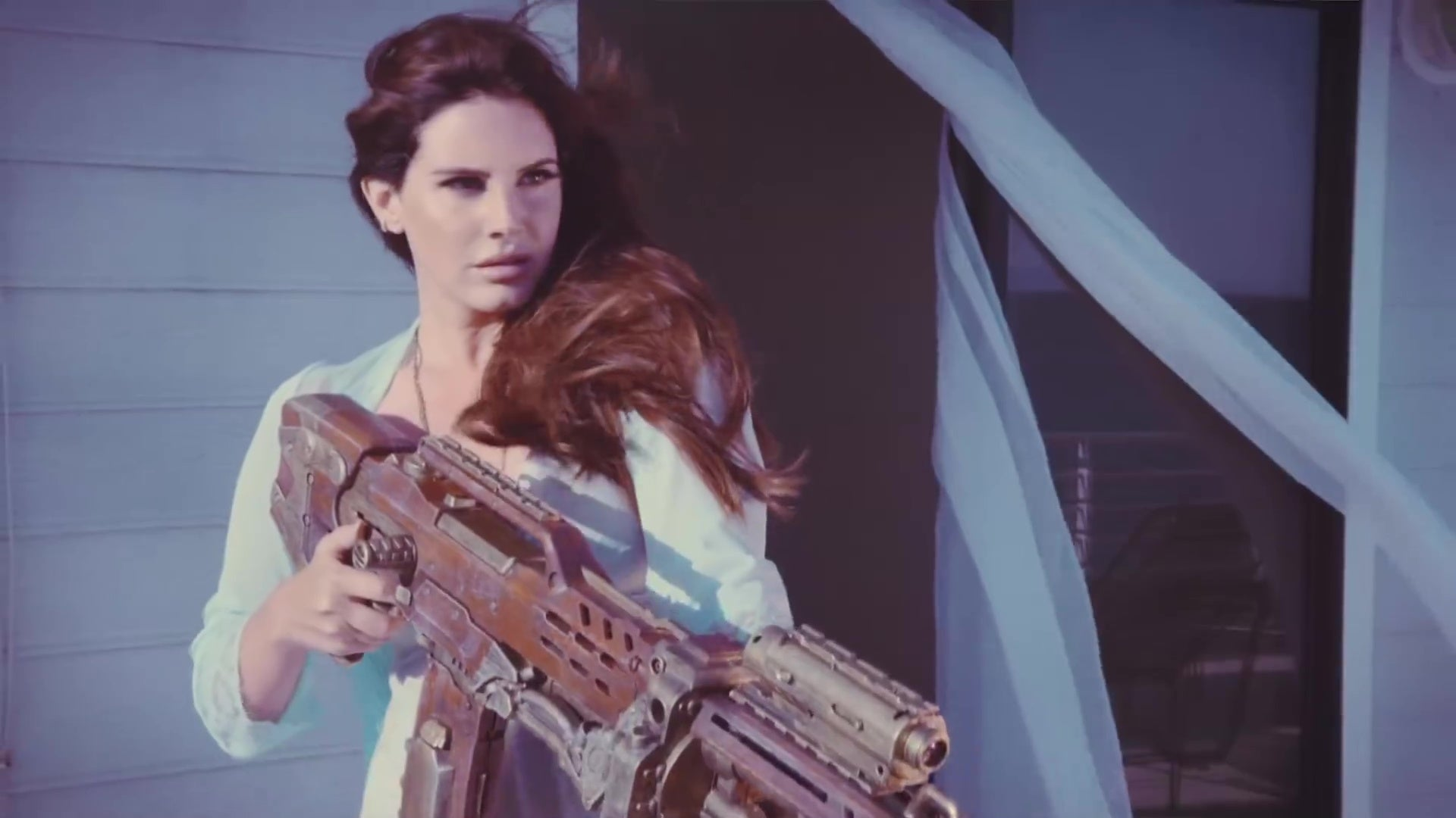 """Lana Del Rey, holding a grenade launcher, in the music video for """"High by the Beach."""""""