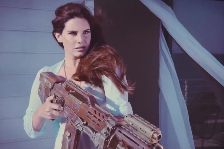"Lana Del Rey, holding a grenade launcher, in the music video for ""High by the Beach."""