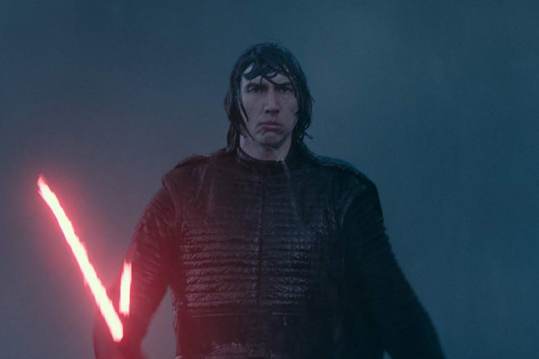 Adam Driver, in a still from The Rise of Skywalker, wearing a black leather suit and coat and wielding his red lightsaber. He looks disappointed.