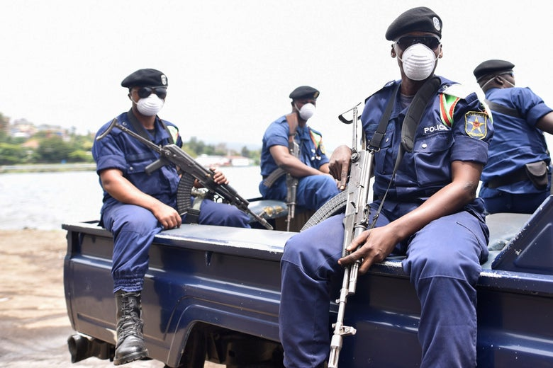 Police wearing masks and holding guns sit in the back of a pickup