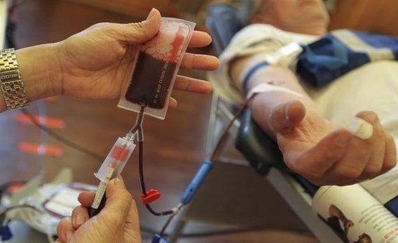 A nurse assists a man donating blood