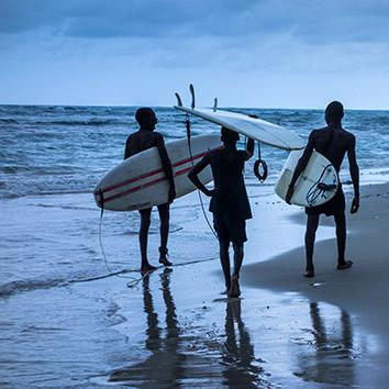 Samuel, Ronald, and Samson walk along the beach at dusk after a successful afternoon in the water, May 5, 2014.