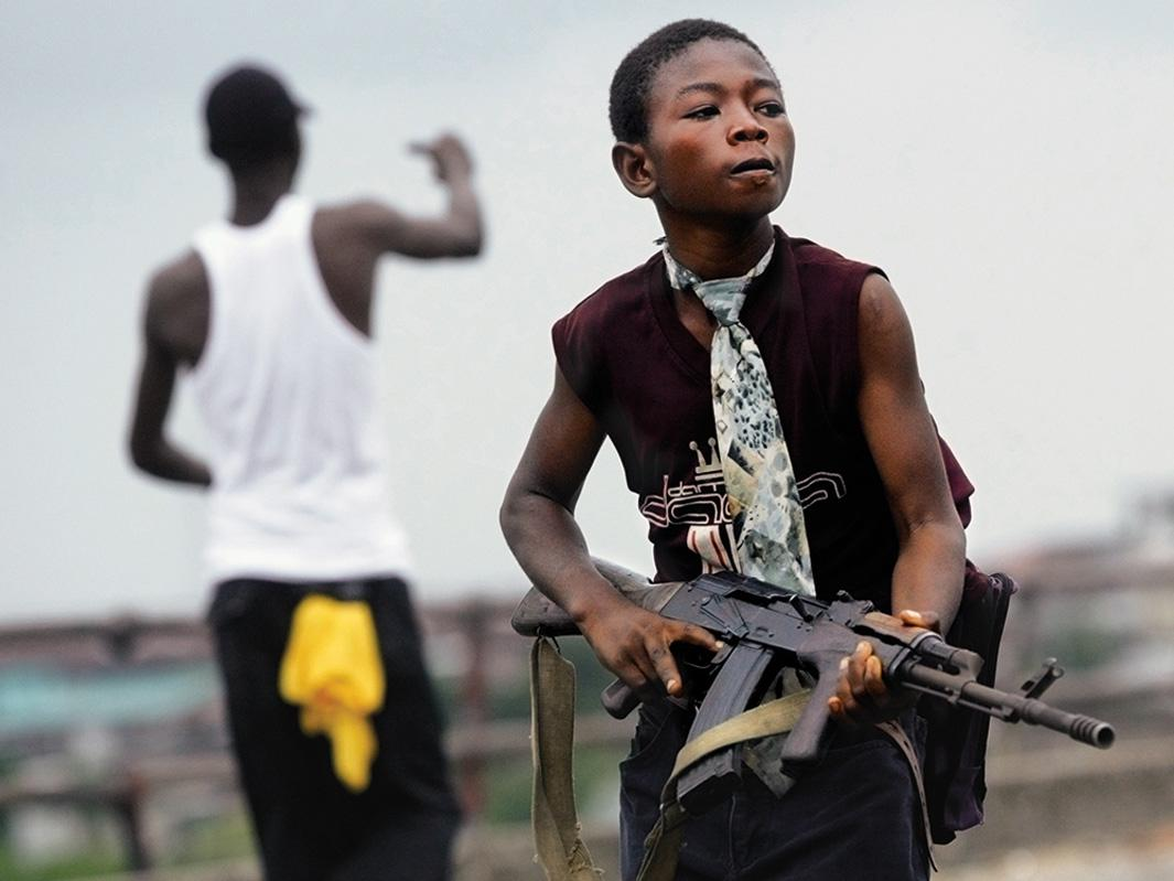 A child Liberian militia soldier loyal to the government walks away from firing on July 30, 2003, in Monrovia, Liberia. Sporadic clashes continue between government forces and rebel fighters in the fight for control of Monrovia.
