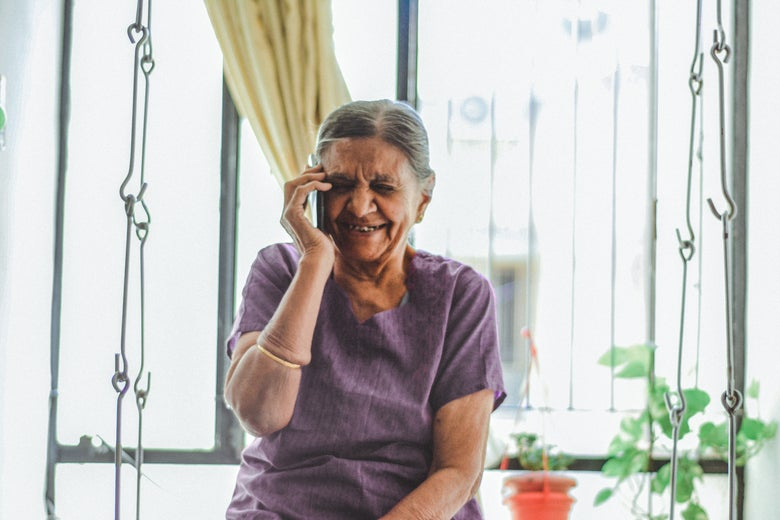An elderly woman listens on a cellphone in front of a window.
