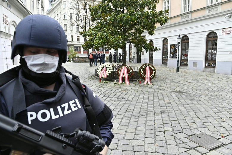 Police stand guard near a crime scene where wreaths have been displayed to pay respects to the victims in the center of Vienna on November 3, 2020, one day after a shooting which left four people dead. - One of the gunmen in the Vienna attack which left four people dead had double North Macedonian-Austrian nationality and a conviction for trying to travel to Syria, the interior minister said on November 3, 2020. (Photo by HANS PUNZ / APA / AFP) / Austria OUT (Photo by HANS PUNZ/APA/AFP via Getty Images)