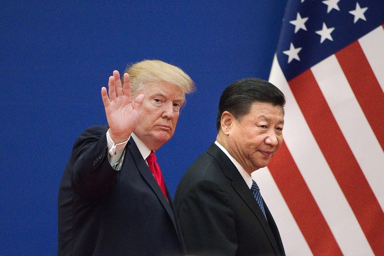 Trump waves as he and Xi walk past an American flag.