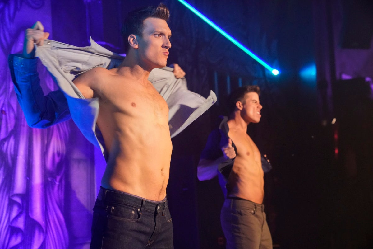 Scott Michael Foster and David Hull take off their shirts onstage in a scene from Crazy Ex-Girlfriend.