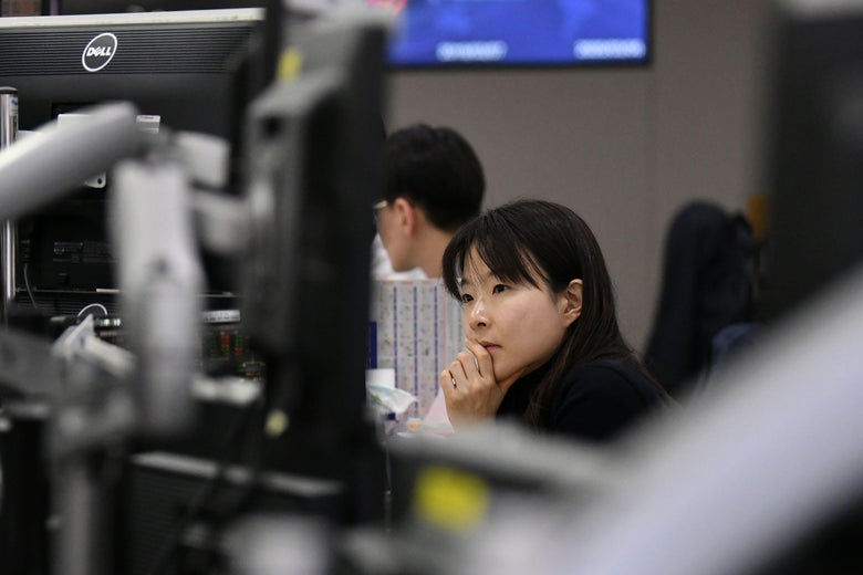 A woman sits at a row of computers and puts her hand on her chin.