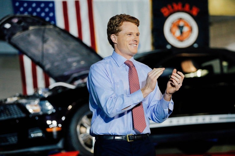 Rep. Joe Kennedy III claps on stage in front of a car and an American flag.