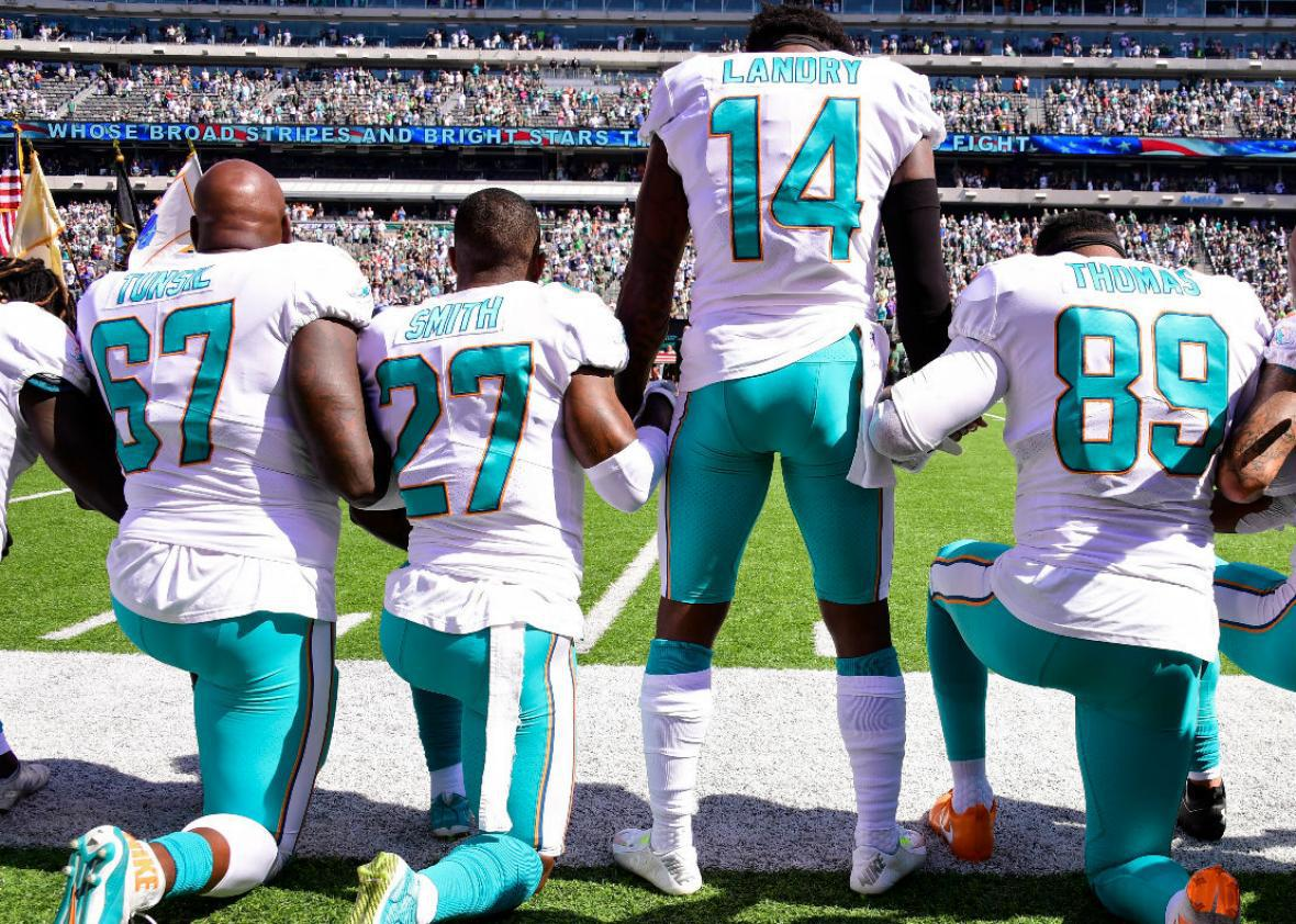 Members of the Miami Dolphins kneel during the national anthem
