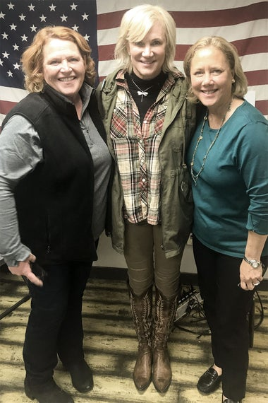 Sen. Heidi Heitkamp, the author, and former Sen. Mary Landrieu pose in front of an American flag.