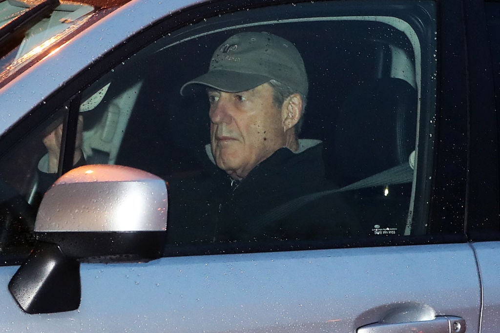 Mueller, wearing a baseball cap and looking pensive, is pictured behind the driver's side window of a car.