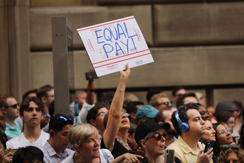 "A woman holds a sign that says ""Equal Pay"" in a crowd of USWNT supporters."