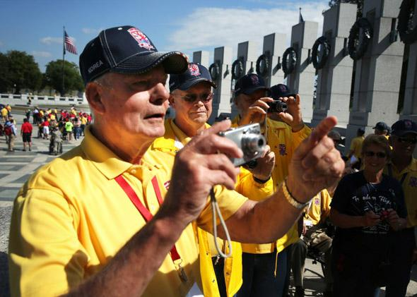 Korean War veteran Bill Bakley, Vietnam War veterans Norman Tjelmeland, and Stanley Twedt, of Ames, Iowa, snap pictures at the World War II Memorial after they were let in during a government shutdown.