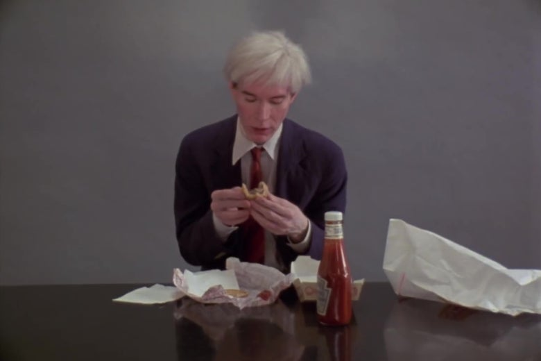 Andy Warhol, folding a Burger King hamburger in half.
