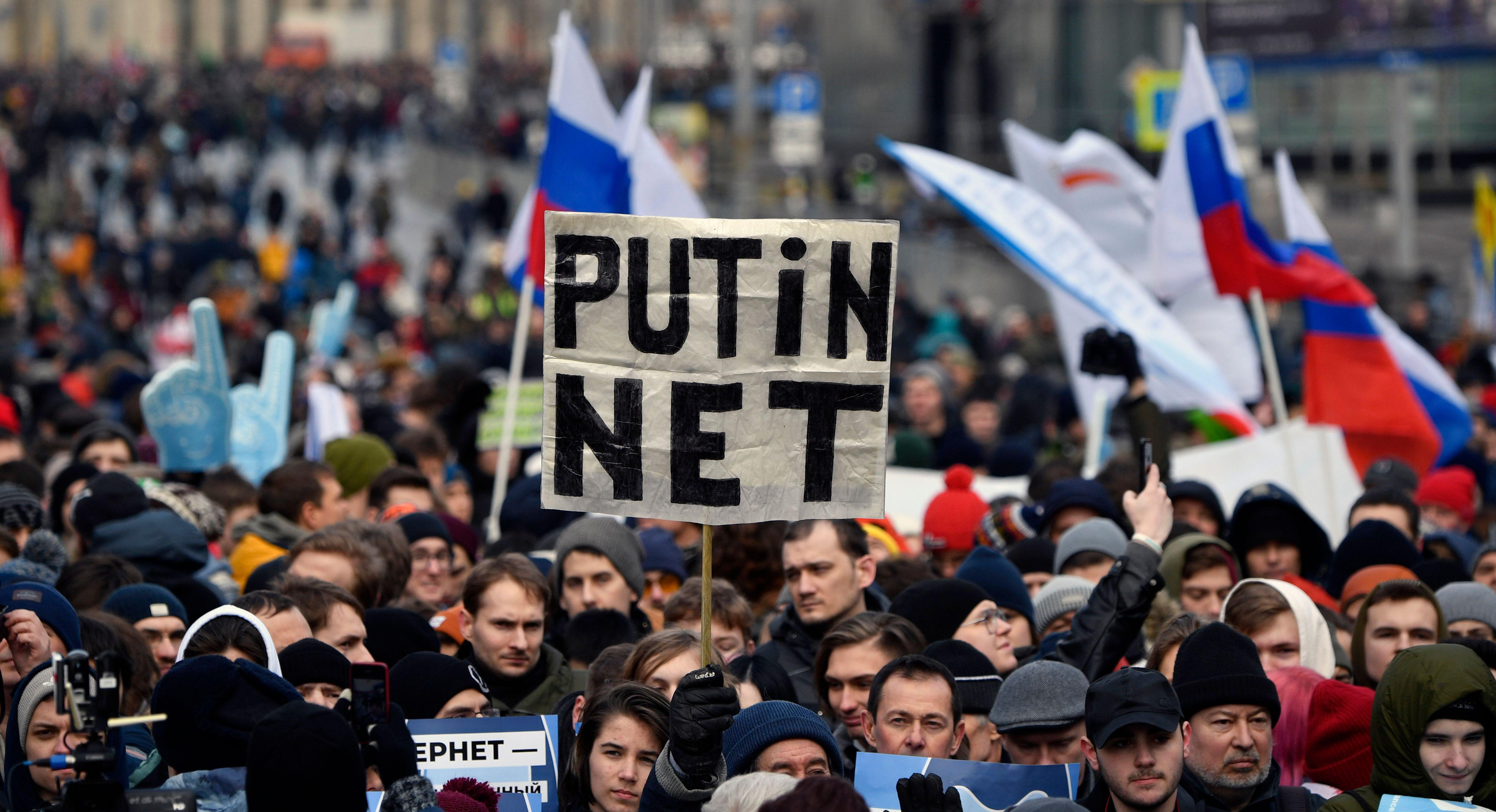 """A protester holds up a sign that reads, """"Putin net."""""""