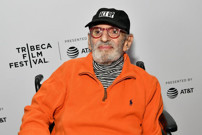 Larry Kramer seated in front of a Tribeca festival backdrop.