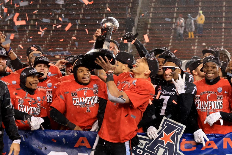 Desmond Ridder holds up the championship trophy after winning the AAC title, surrounded by his celebrating team and falling confetti