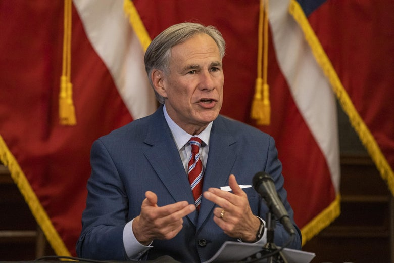 Texas Gov. Greg Abbott speaks in front of American flags, gesturing with his hands.