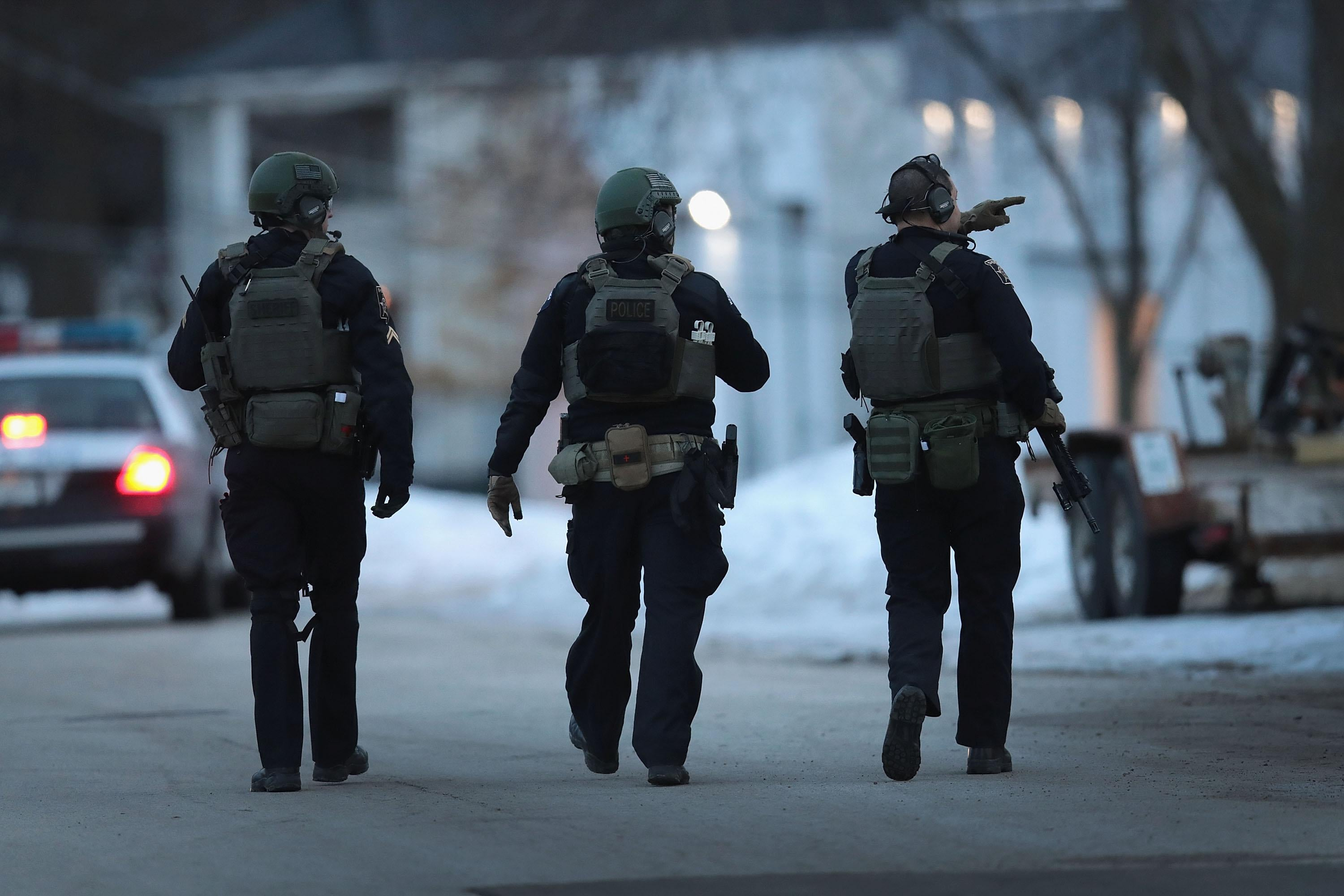 Three officers in bulletproof vests walk on a snowy street, surveying the area.
