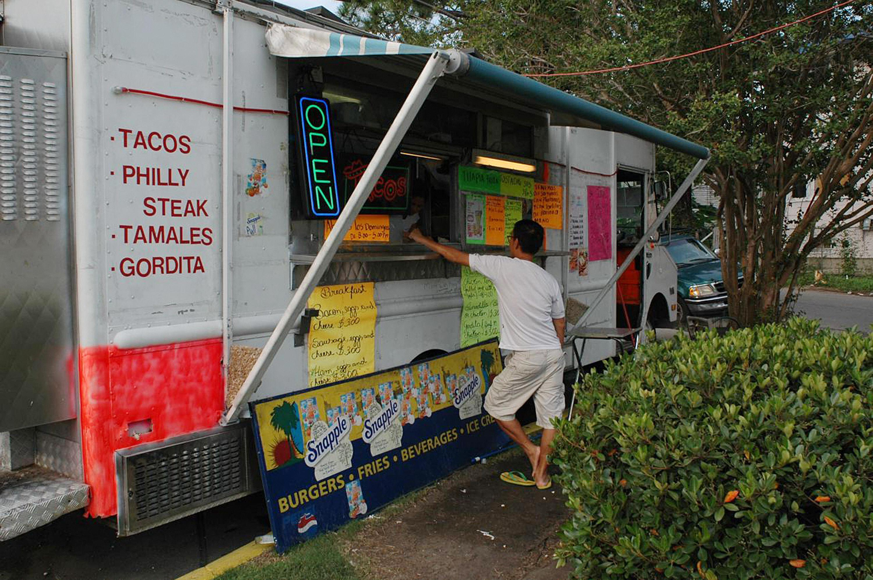 A customer buys food at a mobile Taqueria in New Orleans.
