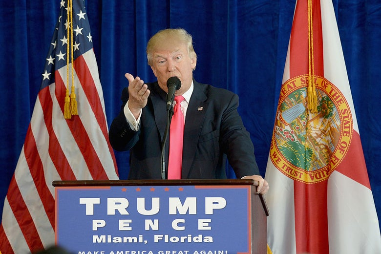 Trump gestures toward the camera while speaking against a blue backdrop.