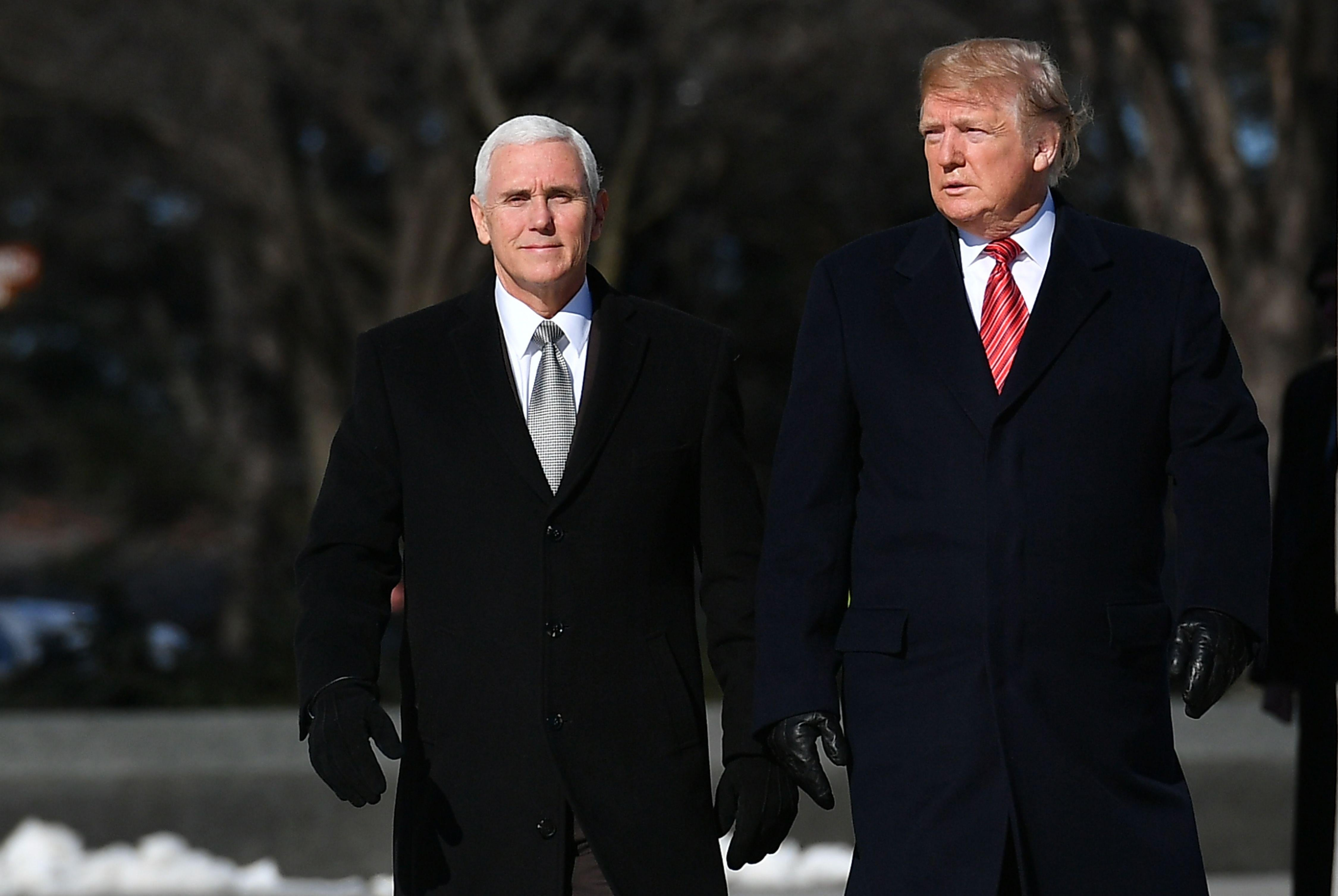 President Donald Trump and Vice President Mike Pence in winter coats and gloves.