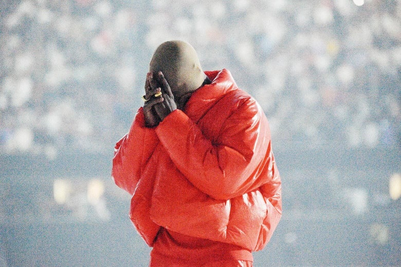 A man wearing a red puffy jacket and matching pants holds his face in his hands.