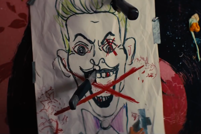 A crude drawing of the green-haired Joker with the letter X drawn over him and knives sticking out of the paper.